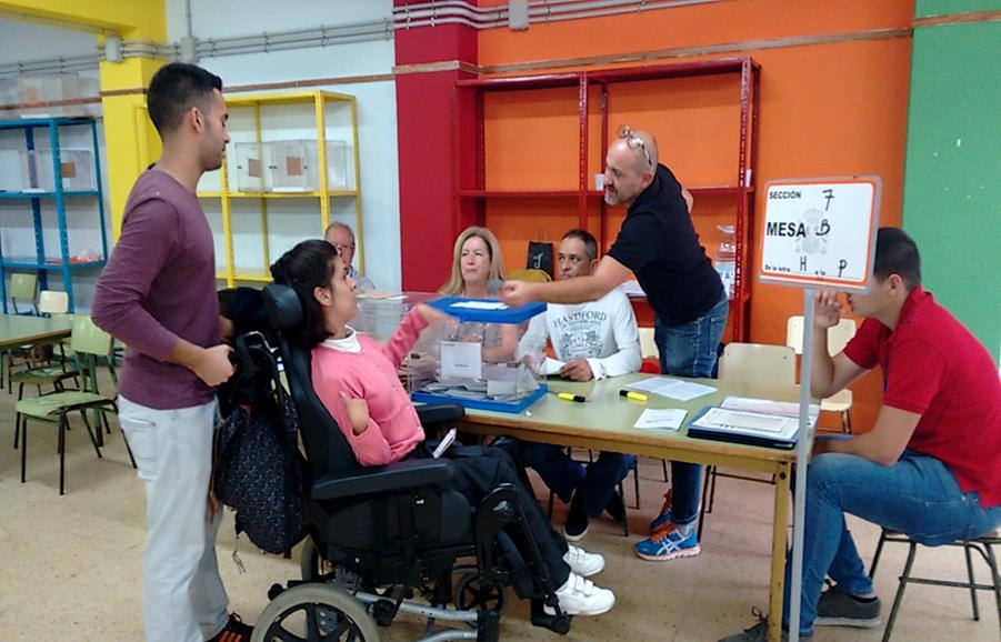 una persona acompaña a otra en silla de ruedas para votar
