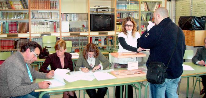 una persona vota en un colegio electoral