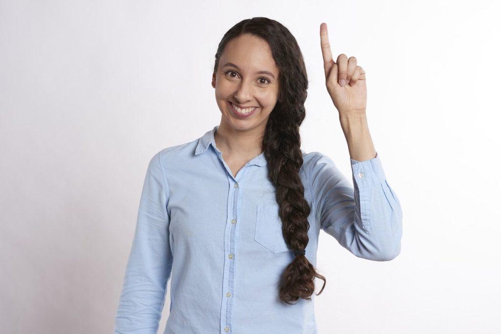 una mujer levanta la mano y sonríe