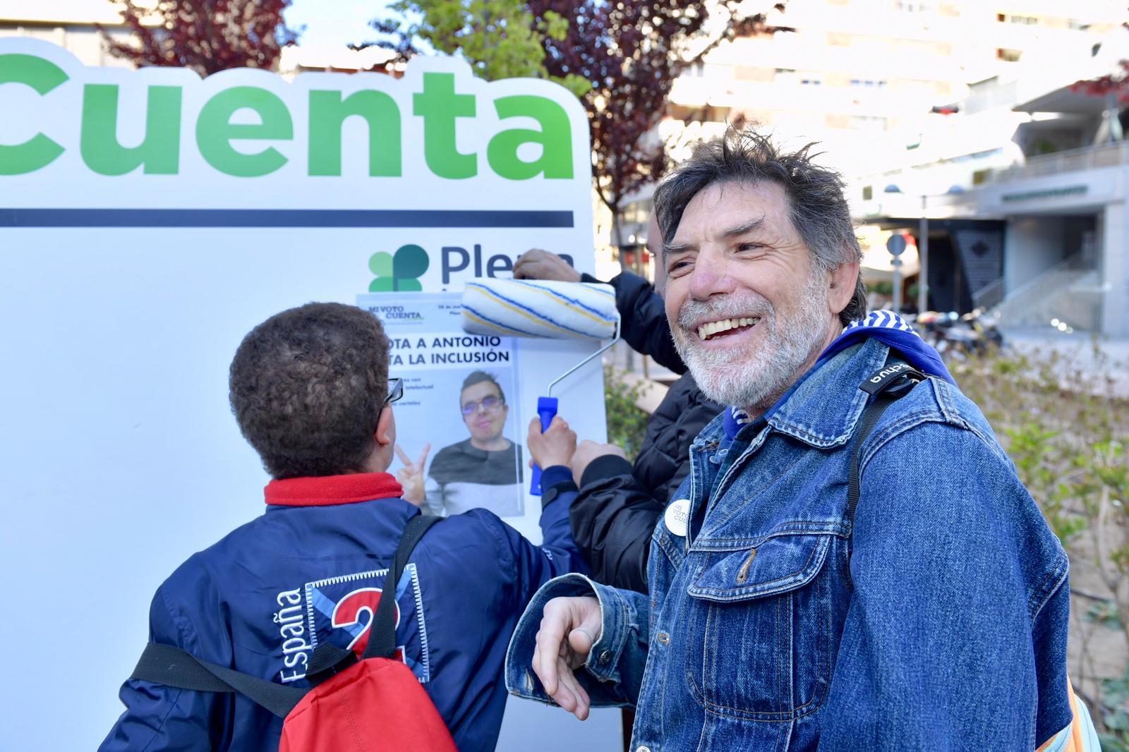 un hombre sonríe en la pegada de carteles