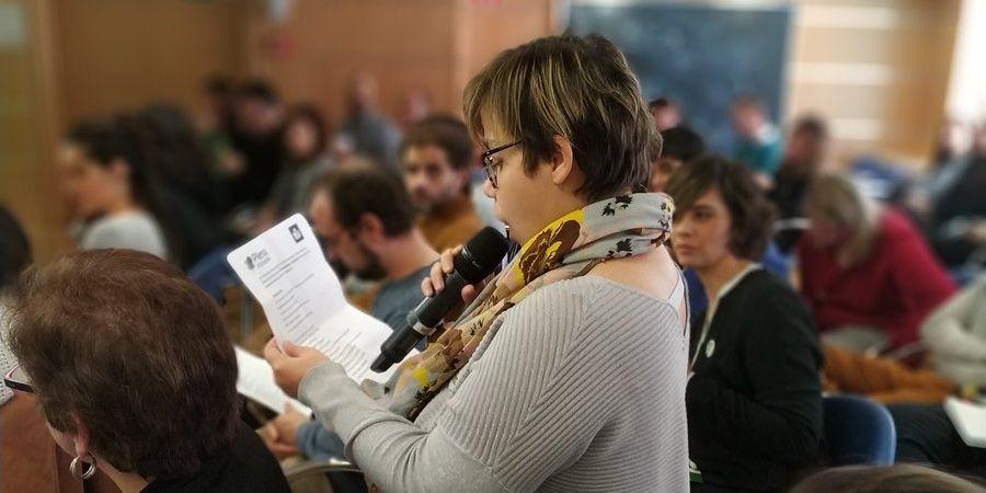 persona lee un papel con un micrófono rodeada de gente