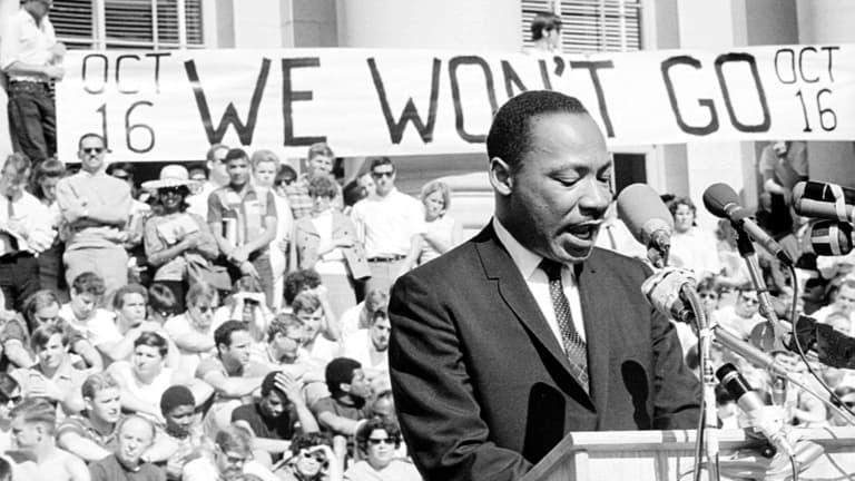 """Martin Luther King habla en un atril y una pancarta detrás reza """"No nos iremos"""". Hay mucha gente detrás también"""